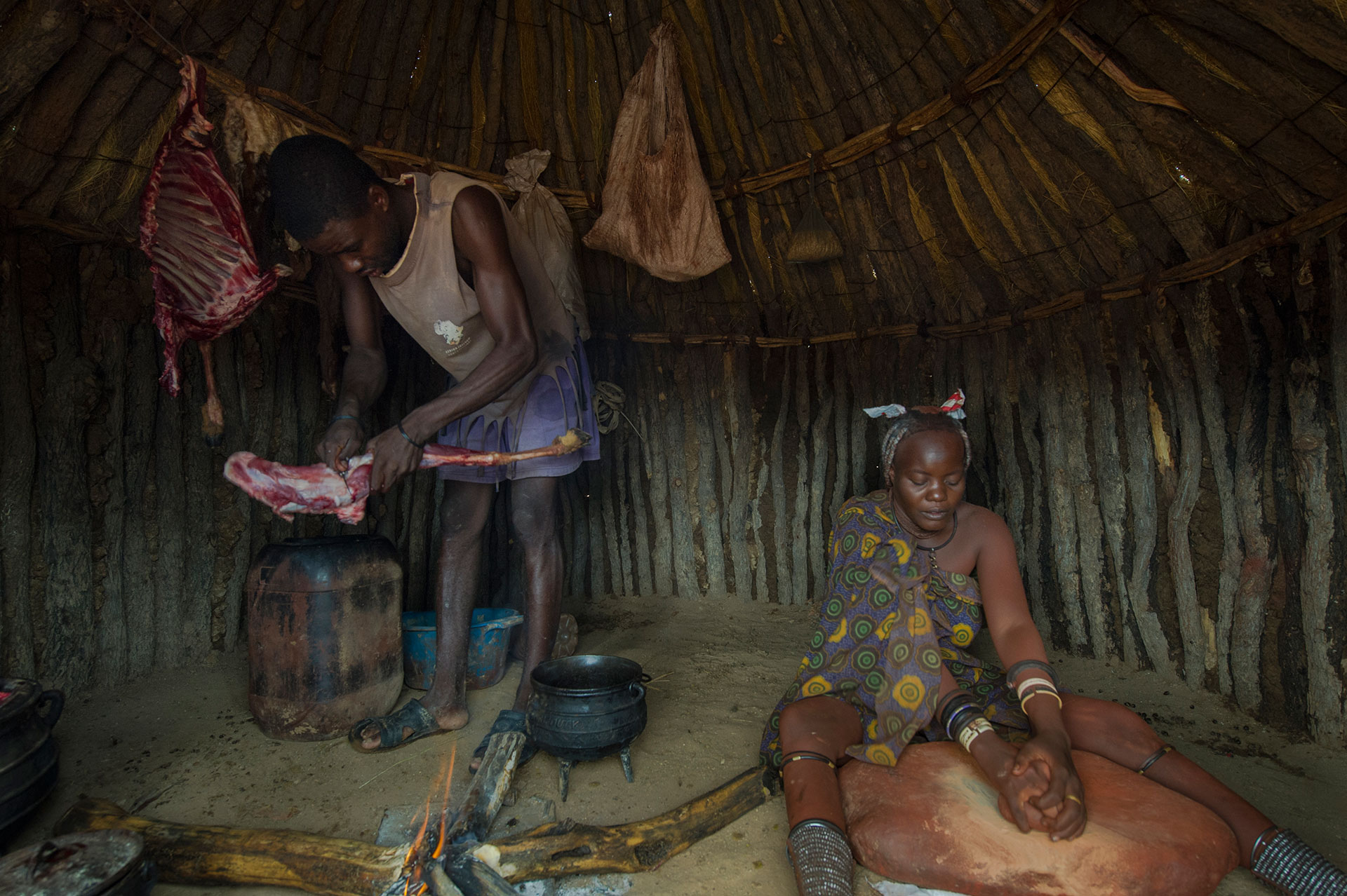 In Afrika in Namibia im Damaraland bei Kamanjab in einem Himbadorf breitet eine Himbafrau die Schutzcreme Okra her und Ihr mann bereitet eine Ziegenkeule zu