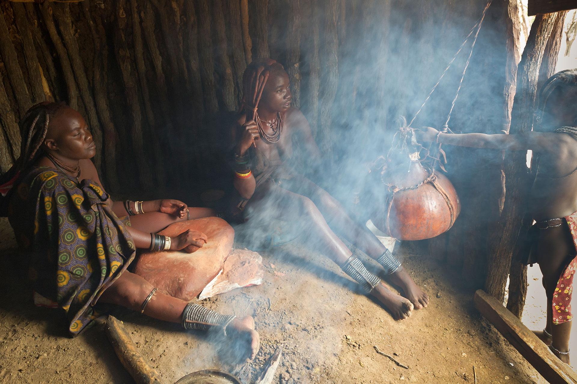 Afrika Namibia im Damaraland bei Kamanjab stellen Frauen in einer Hütte die Schutzcreme, das Okra her