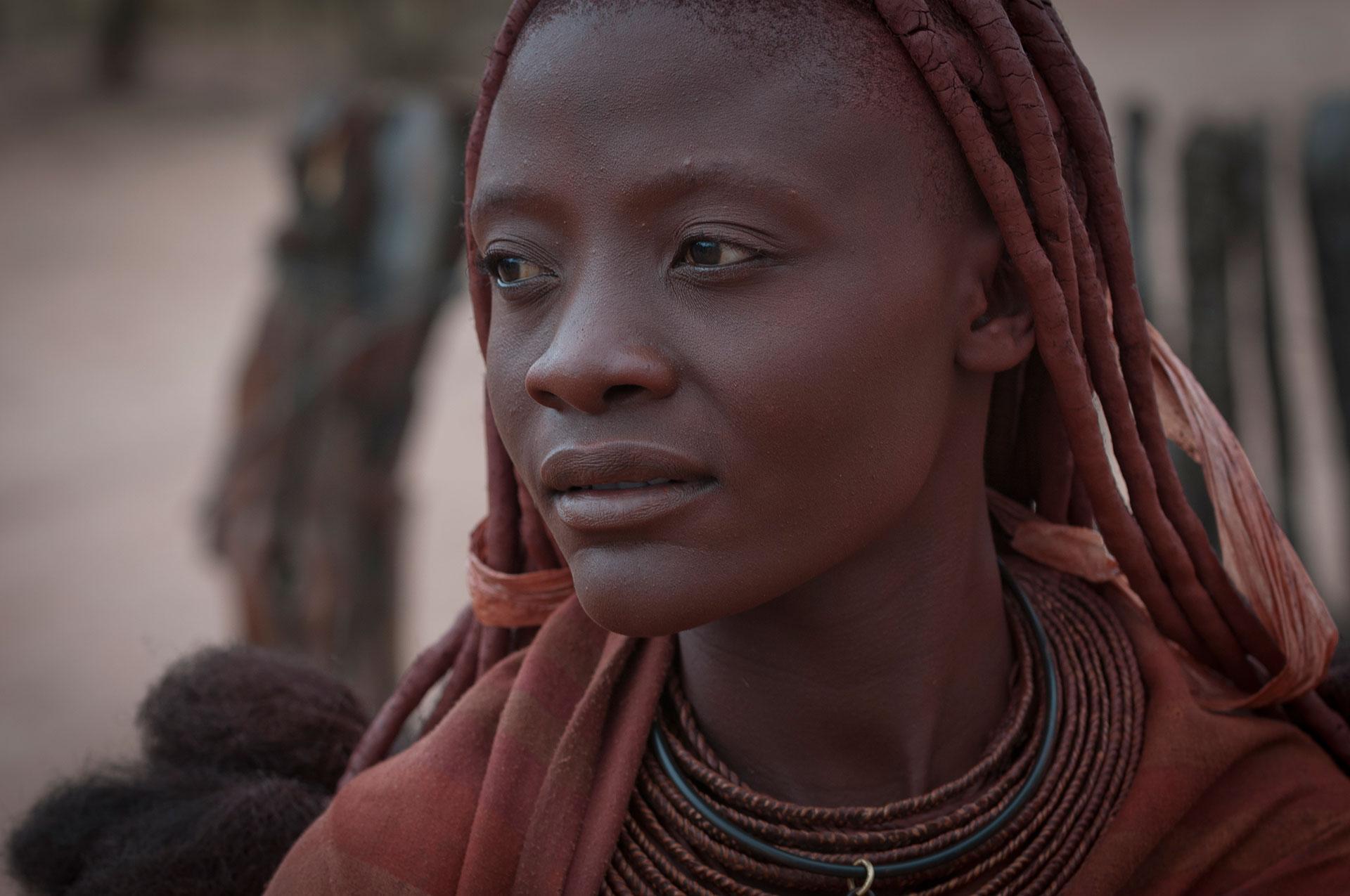 Afrika im Damaraland bei Kamanjab das Portrait einer Himbafrau Ureinwohnerin in einem Hüttendorf