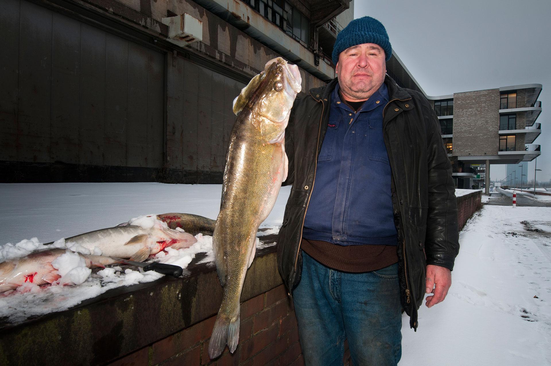 In Bremen in der Überseestadt am Europahafen zeigt ein Angler aus der Ukraine seinen kapitalen Fang einen Zander
