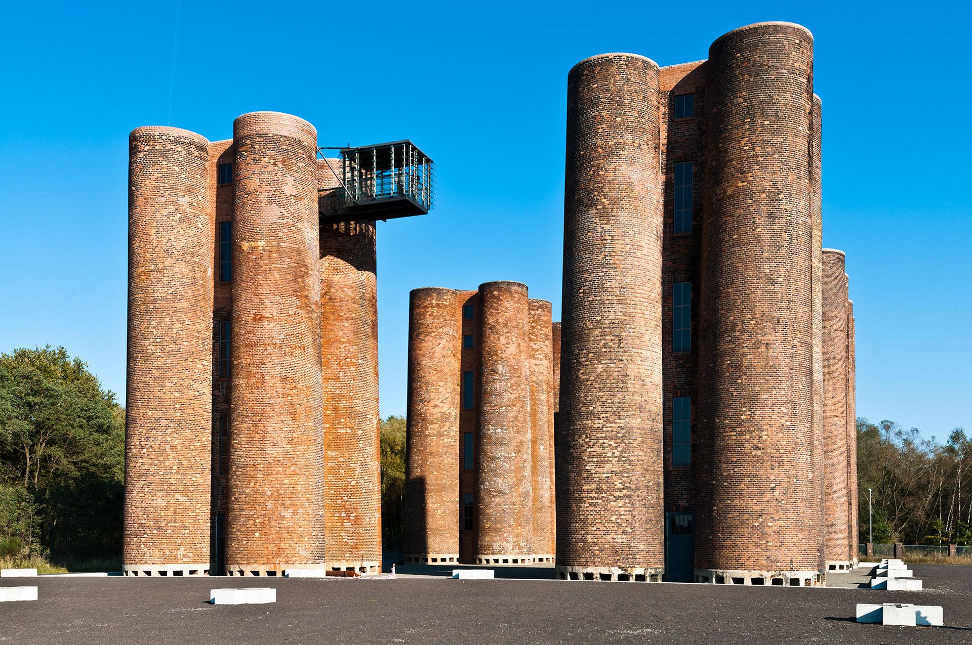 In der Niederlausitz in Lauchhammer stehen diese Backsteintürme. Bei der Koks-Produktion fielen auch große Mengen von phenolhaltigem Abwasser an. Dieses wurde in einer sogenannten Turmtropfkörperanlage mithilfe von Bakterien gereinigt: den Biotürmen.