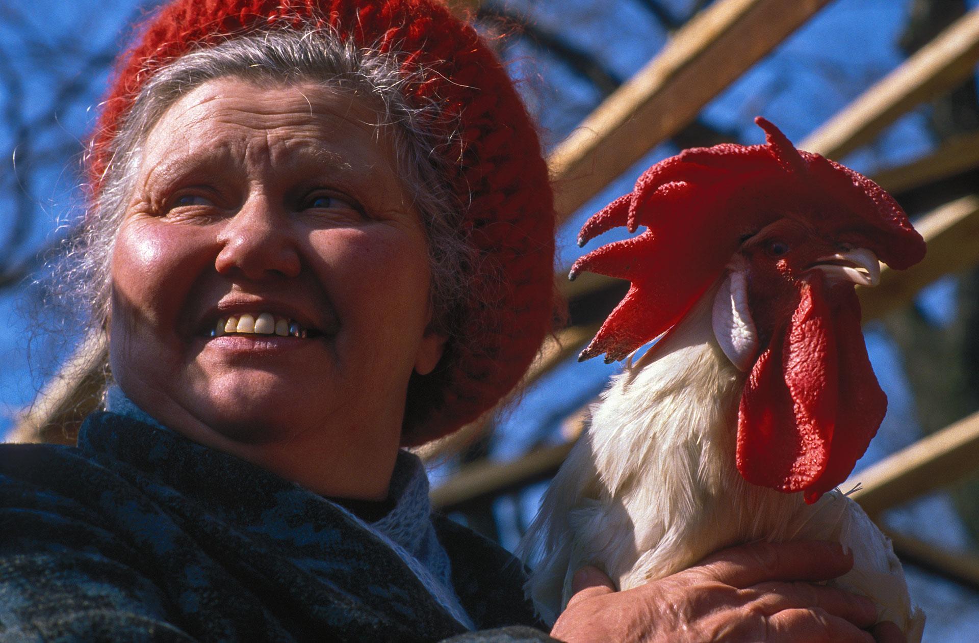 Russland Moskau auf dem Vogelmarkt bietet eine Frau einen Hahn zum Verkauf an