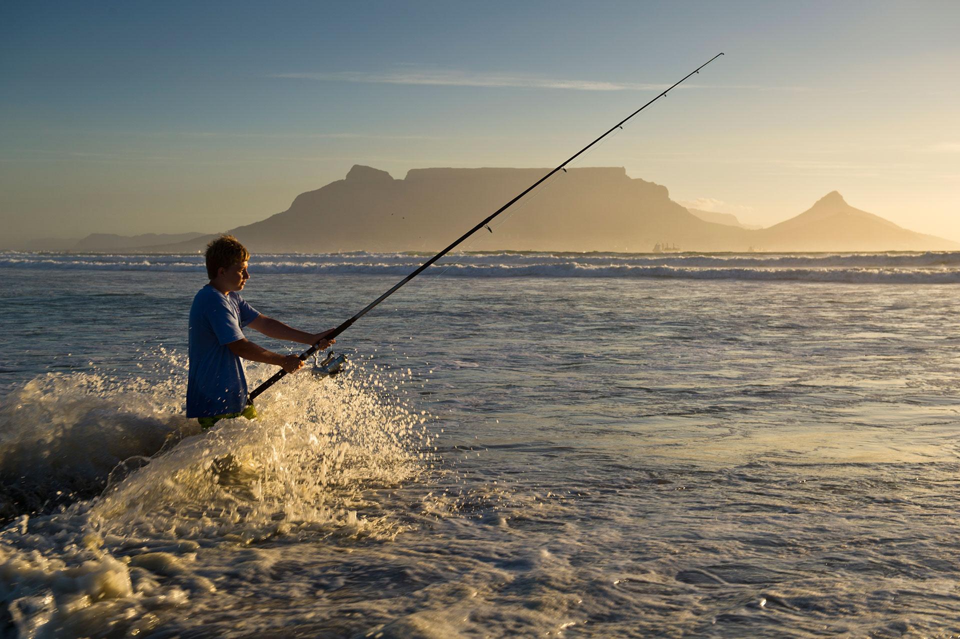 Südafrika in Kapstadt junger Angler in der Brandung vor dem Tafelberg