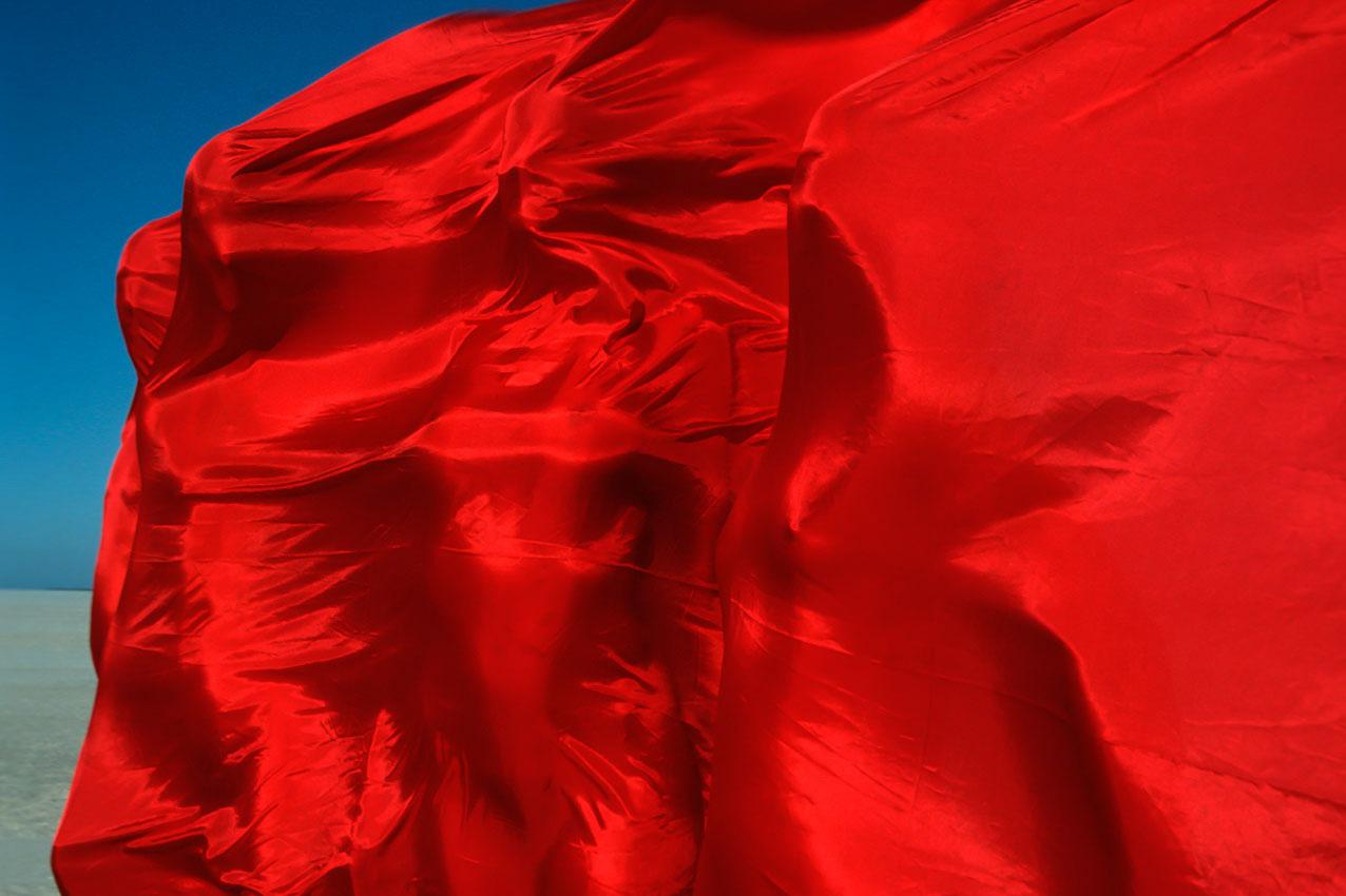 St. Peter-Ording Kunstaktion mit jungen Frauen unter einem roten Tuch