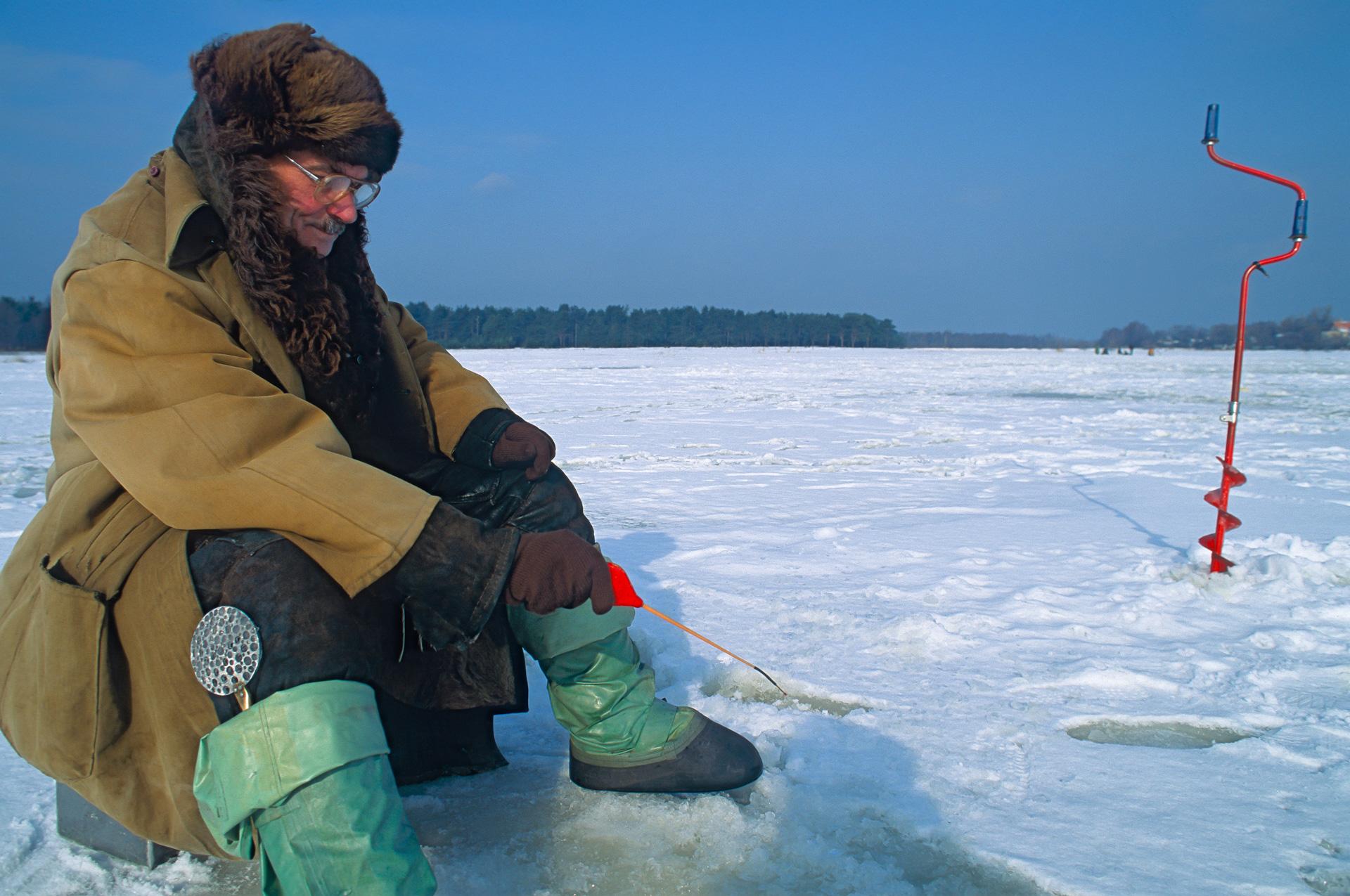 Winter im Baltikum in Lettland an der Ostsee bei Vecaki sitzen Eisangler am zugefrorenen Vecdaugava See