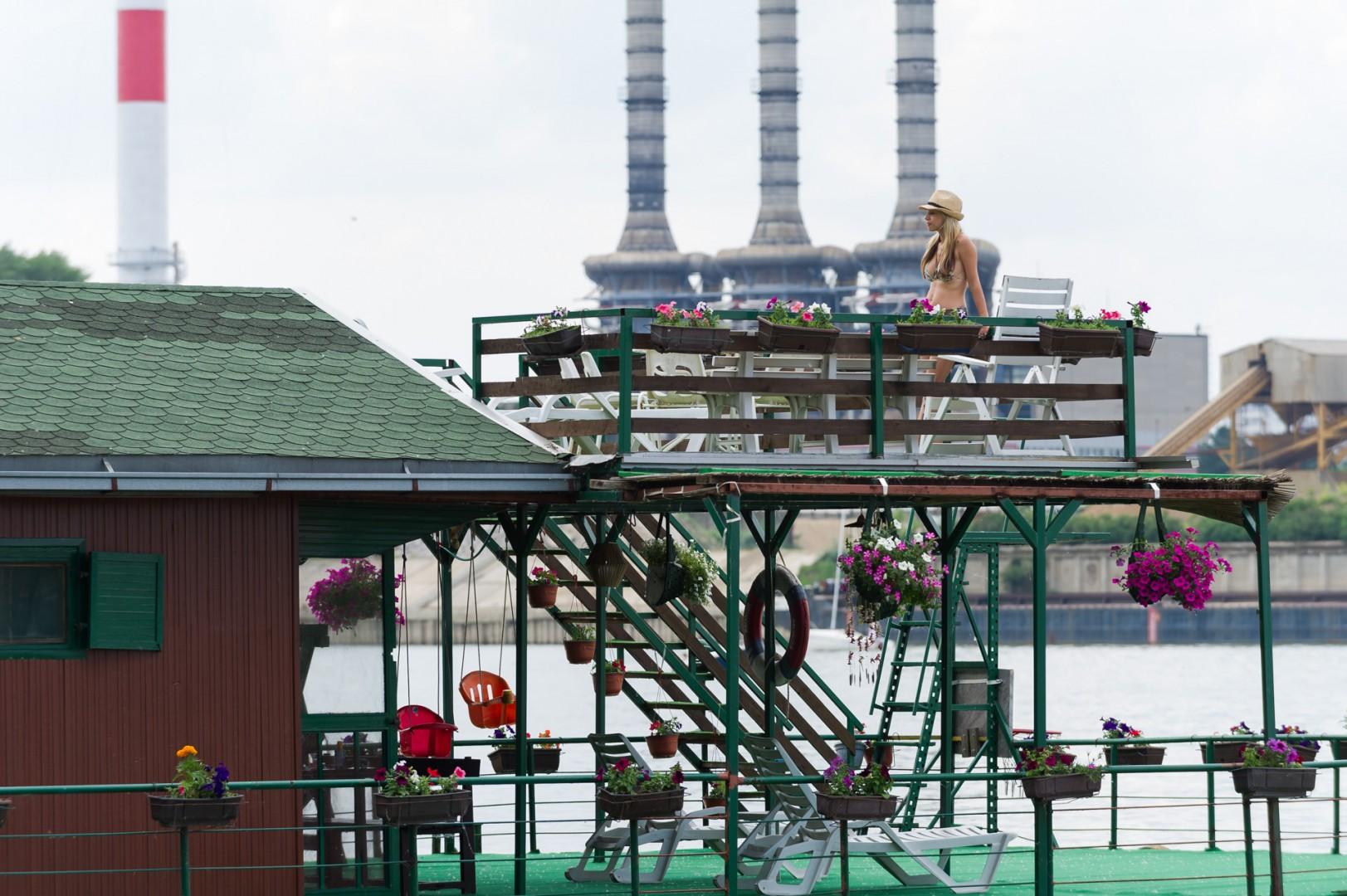 Eine Fabrik mit drei Schornsteinen Junge Frau auf der Terrasse