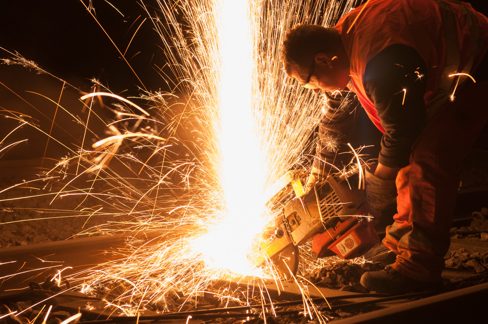 Workers at cutting work in track laying construction with sparks