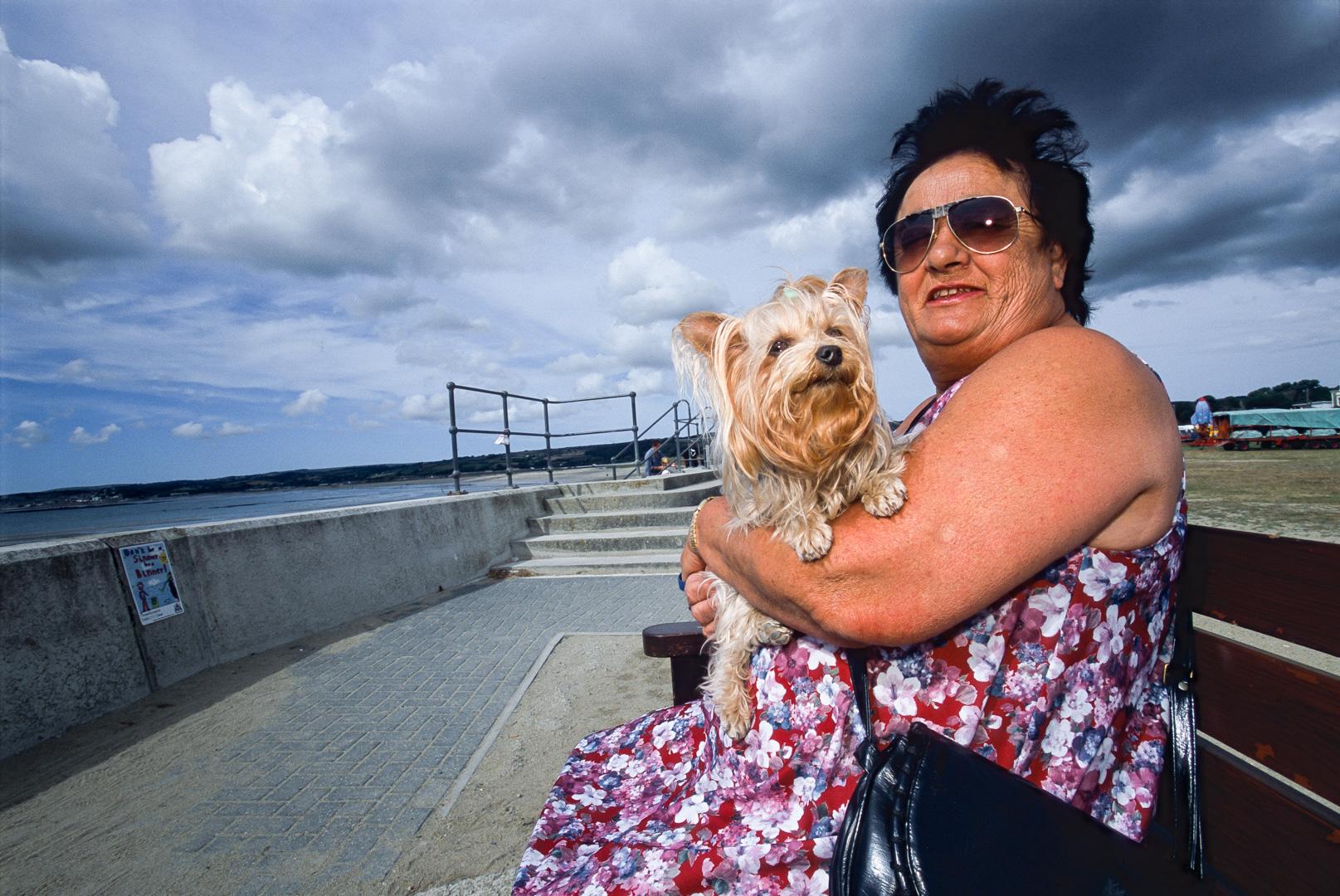 UK-Cornwall England Frau mit Hund auf einer Parkbank an der Uferpromenade