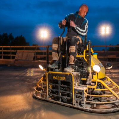 Arbeiter auf der Aufsitz-Glättmaschine nach der Betonage einer Autobahnbrücke in der Nachtschicht.